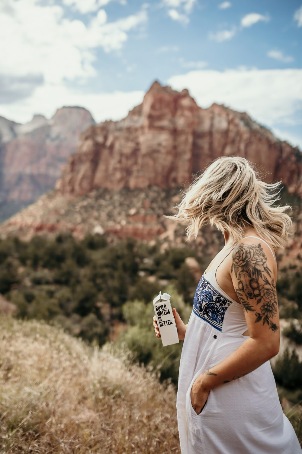 woman holding 500 mL of Boxed Water at the mountain