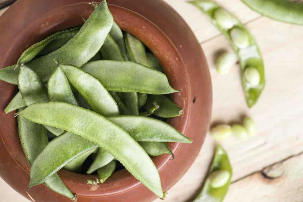 green snow peas in brown pot