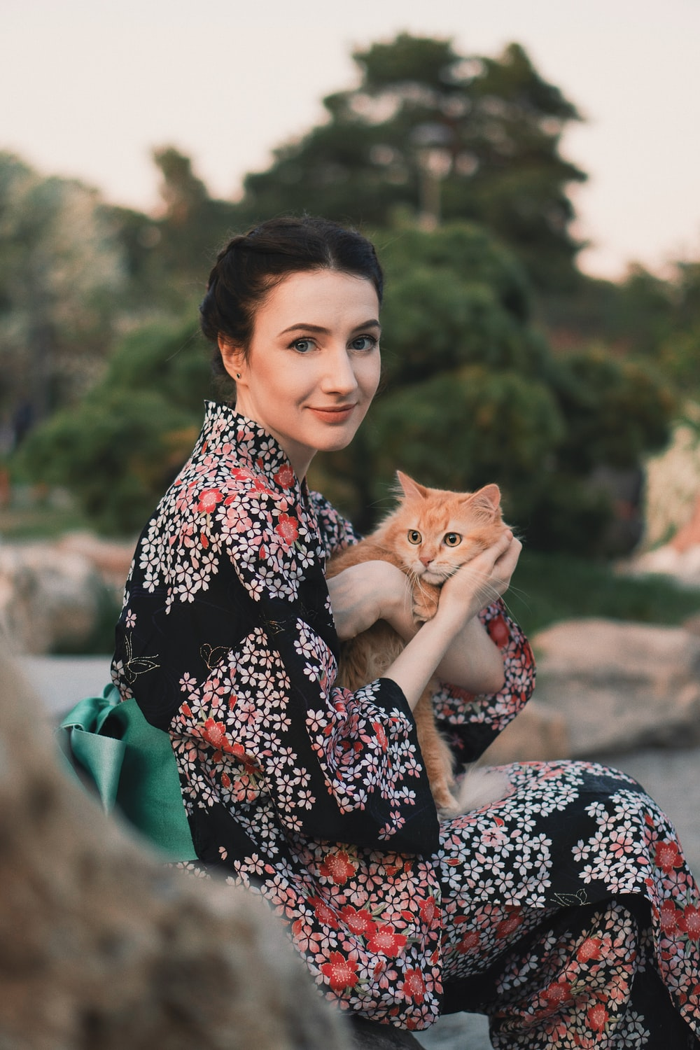 woman holding orange cat during daytime