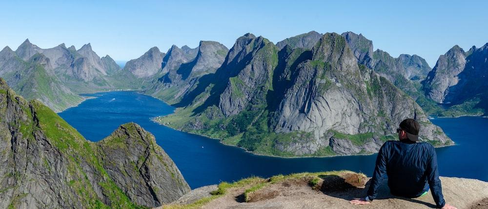 man sitting on mountain during daytime