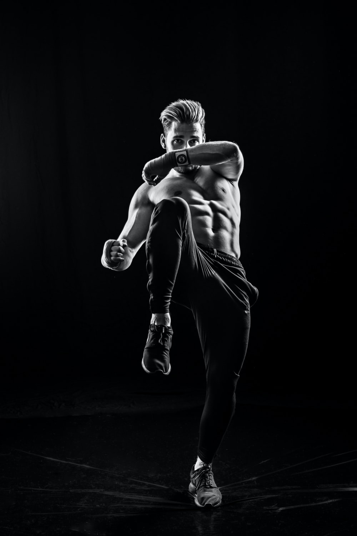 grayscale photo of man wearing pants kicking