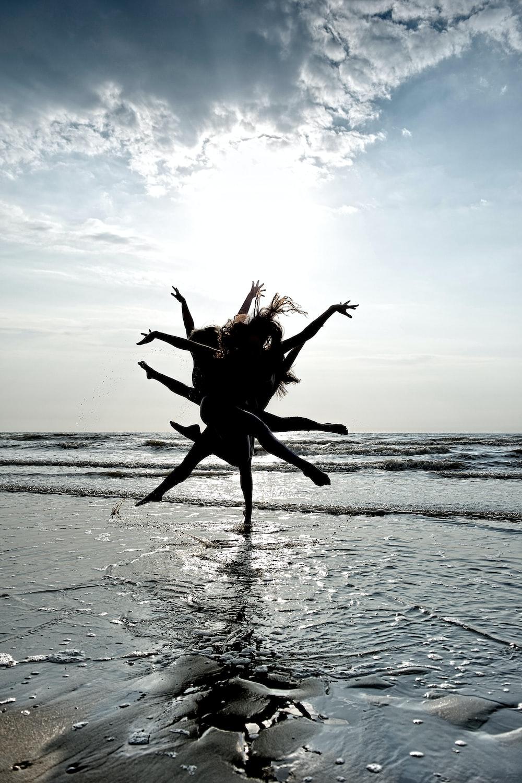 people dancing near seashore