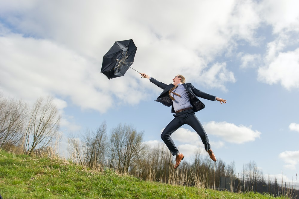 man holding umbrella while jumping on green field under blue and white skies