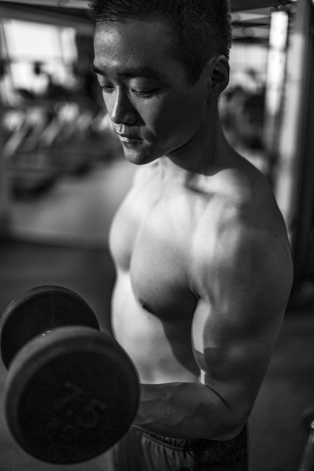 man lifting dumbbell inside gym