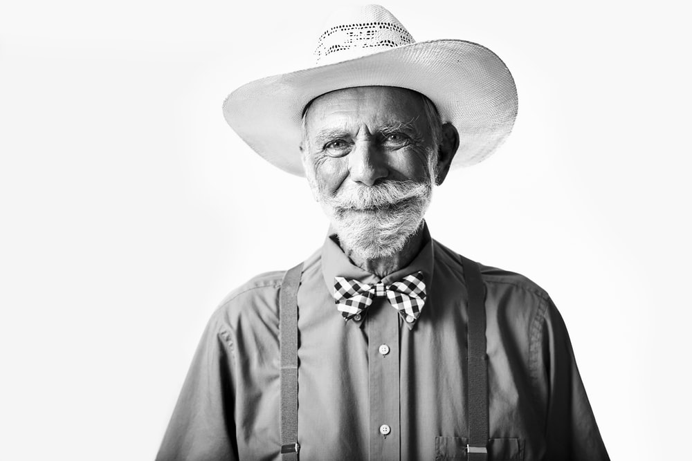 man in collared shirt with cowboy hat