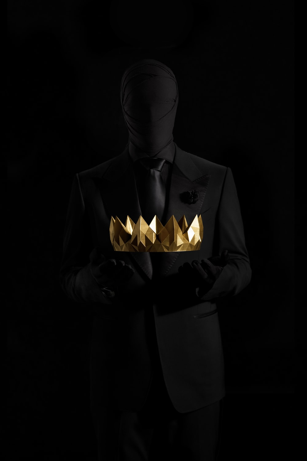 person in black suit jacket holding gold crown