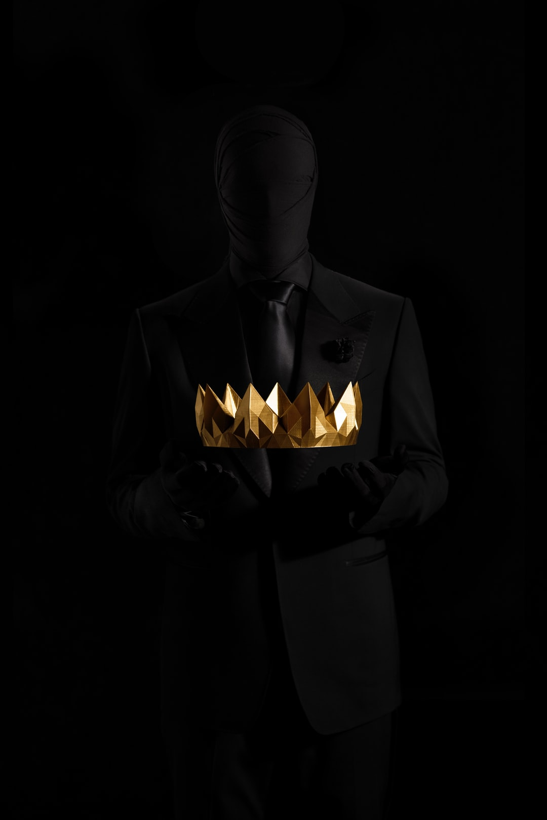 Silhouette holding gold crown