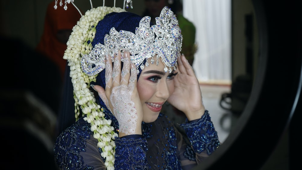 woman wearing blue abaya dress and silver crown smiling