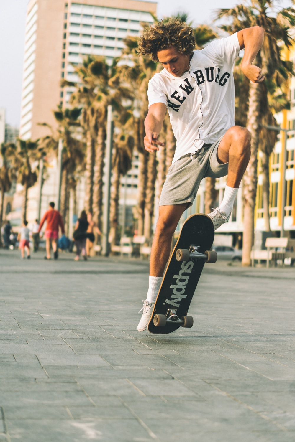 man wearing white and black t-shirt skating on road near buildings