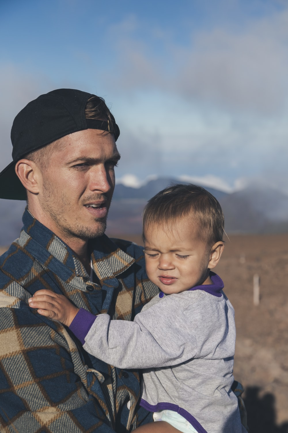 shallow focus photo of man carrying baby