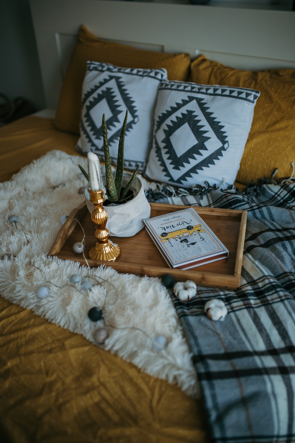 taper candle, book, and potted plant on a tray placed on top of bed