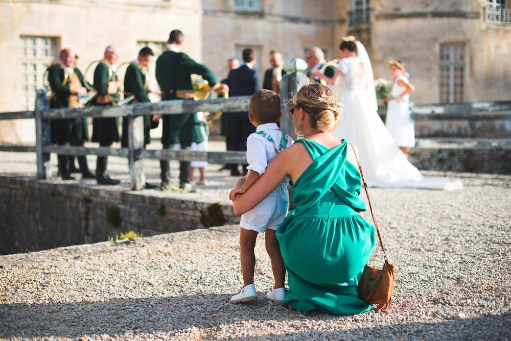 woman in green gown sitting beside standing boy near bridge