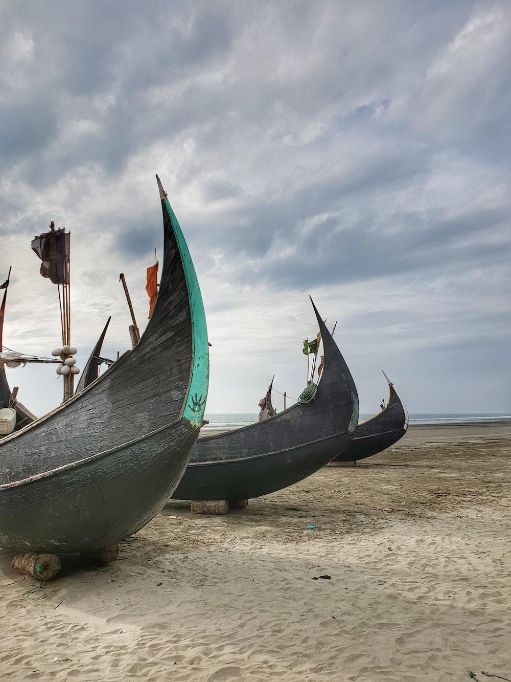 grey wooden boats on seashor