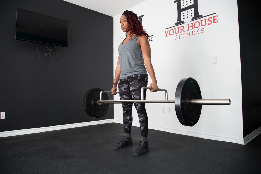 woman standing and lifting barbell
