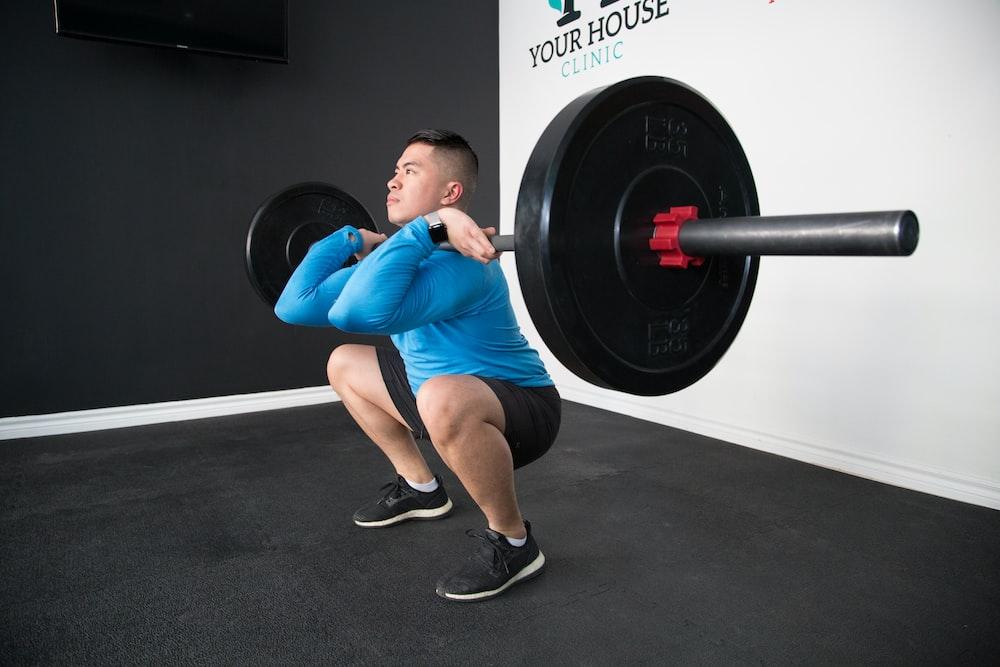 man sitting and lifting black barbell