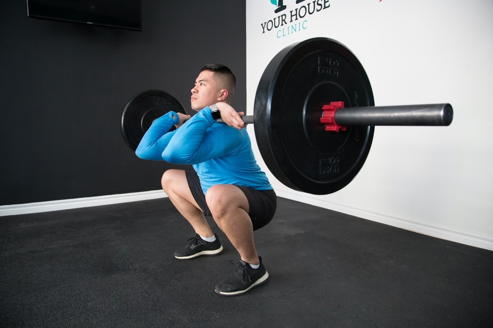 man sitting and lifting black barbell