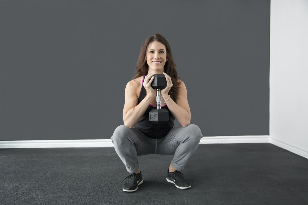 smiling woman holding dumbbell while sitting