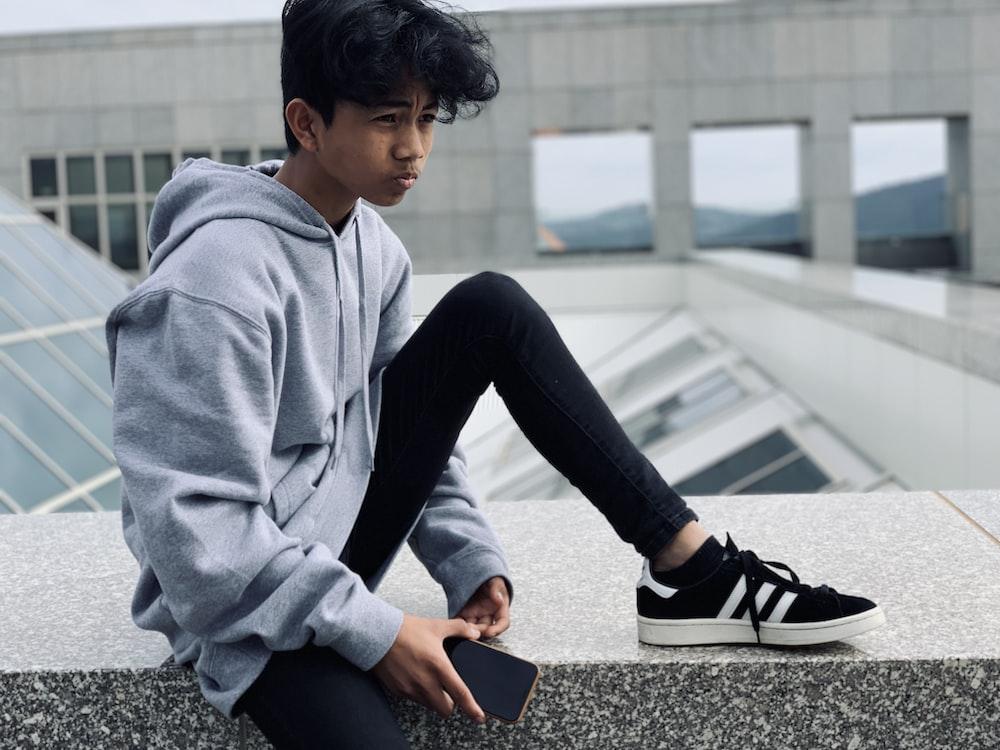 boy sitting on gray concrete