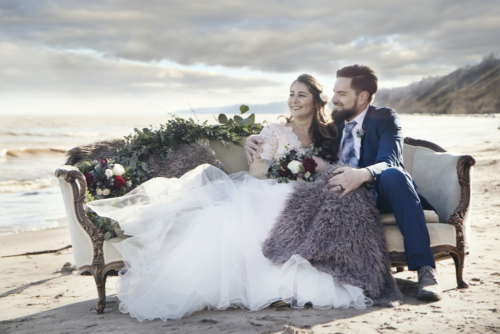 man and woman sitting on padded sofa beside sea