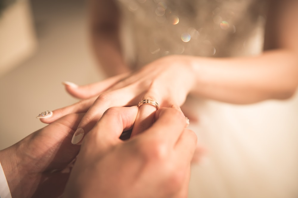 man holding gold ring on woman's finger