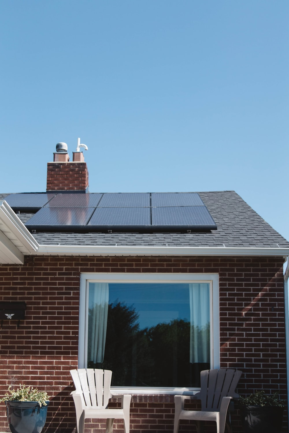 brown brick house with solar panels on roof