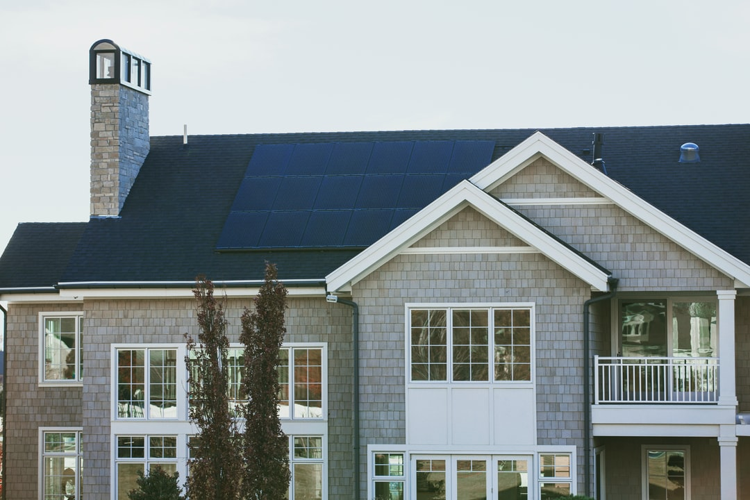 Vivint Solar - Solar Panels on a large seaside home with chimney and many windows.