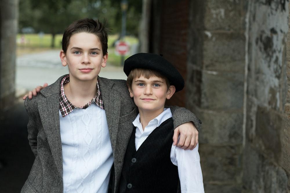 two boys beside concrete wall