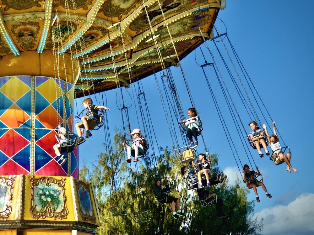 toddler riding in amusement park during daytime