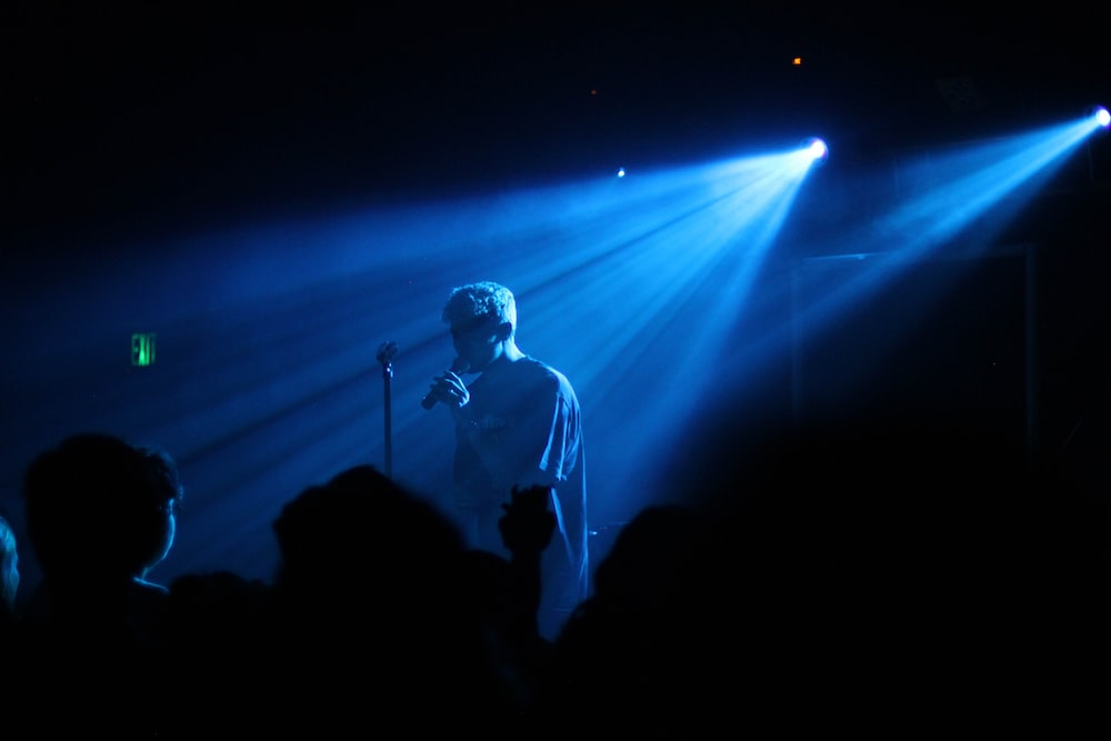 photo of man performing on stage