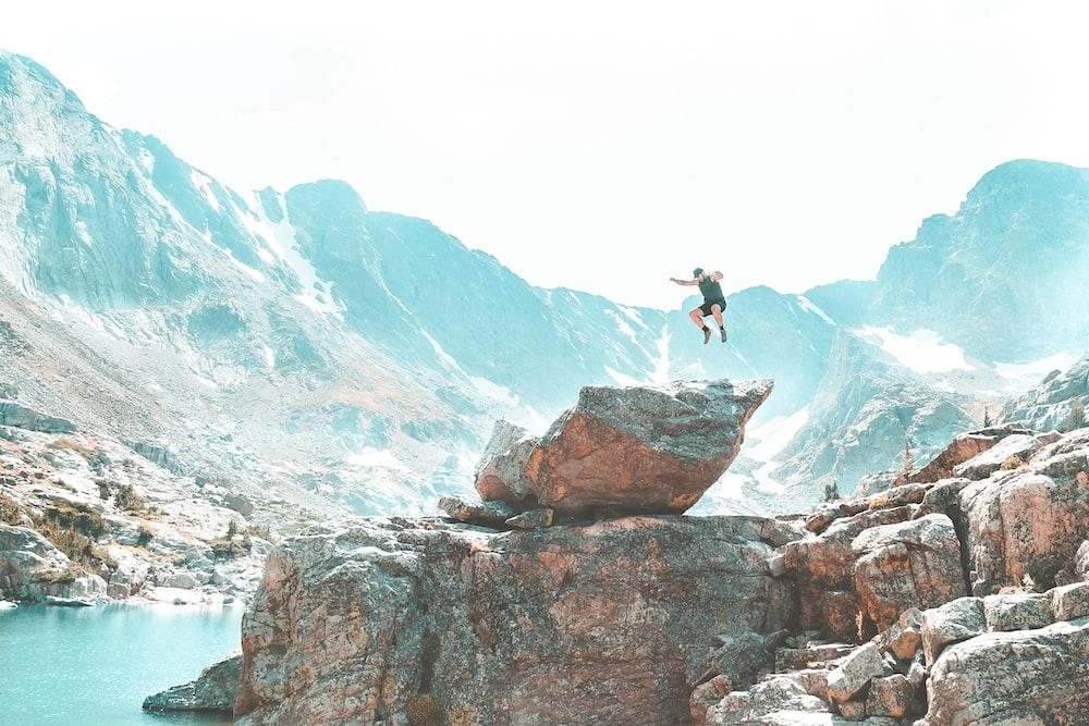 man jumping on boulder