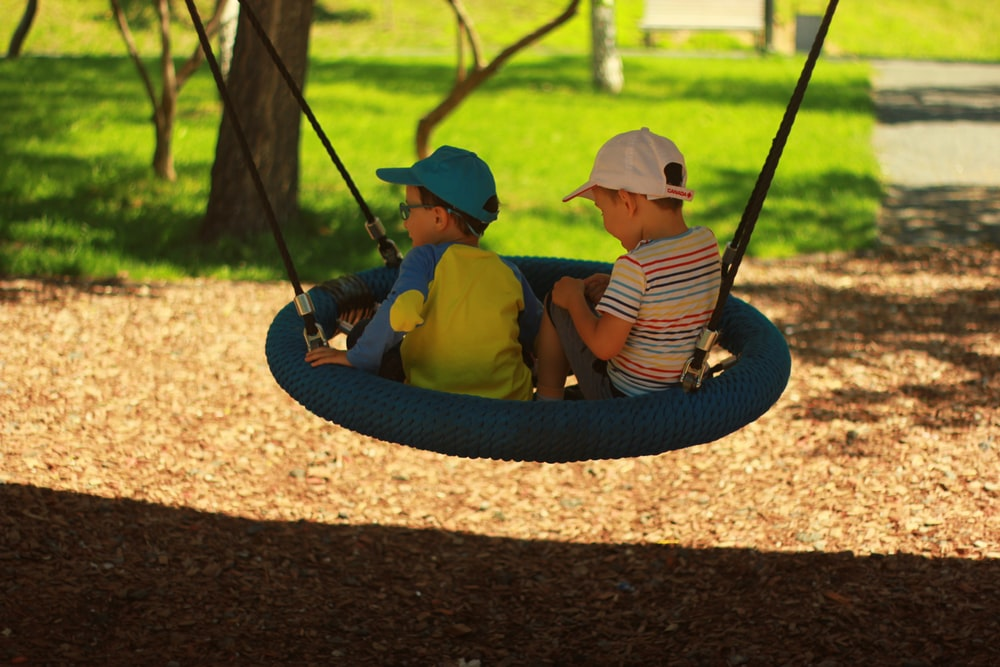 two boys sitting on swing