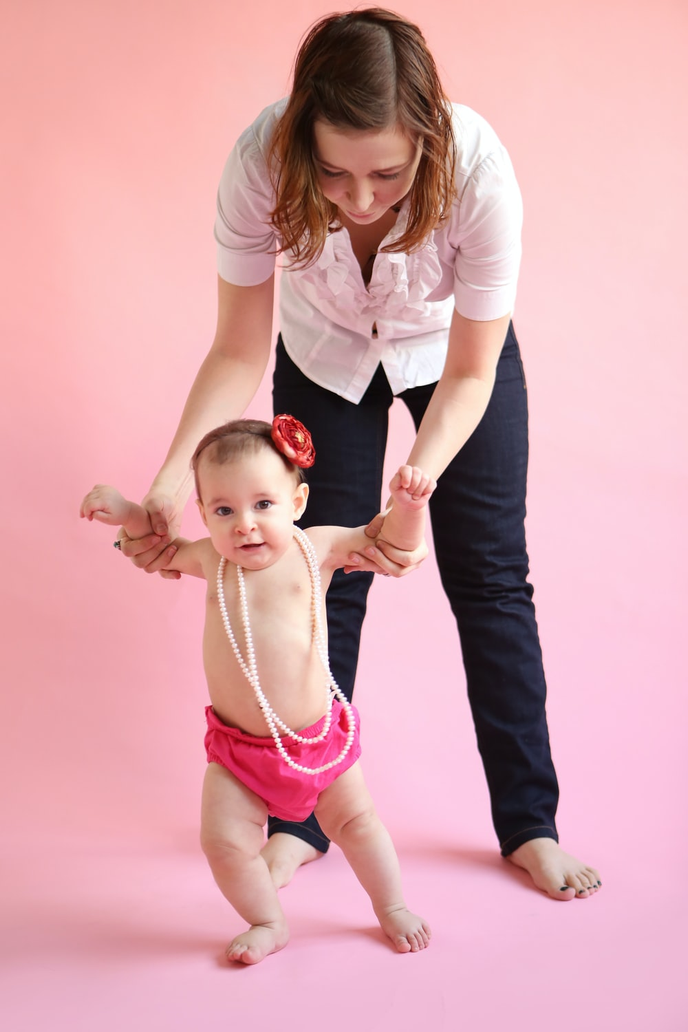 barefooted woman standing and assisting baby while walking