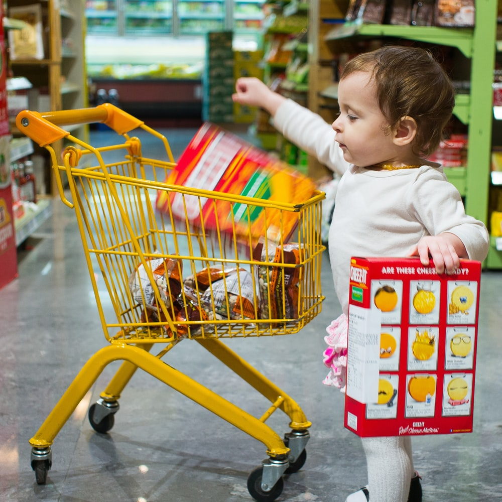 toddle carrying red and white box standing beside yellow shopping cart