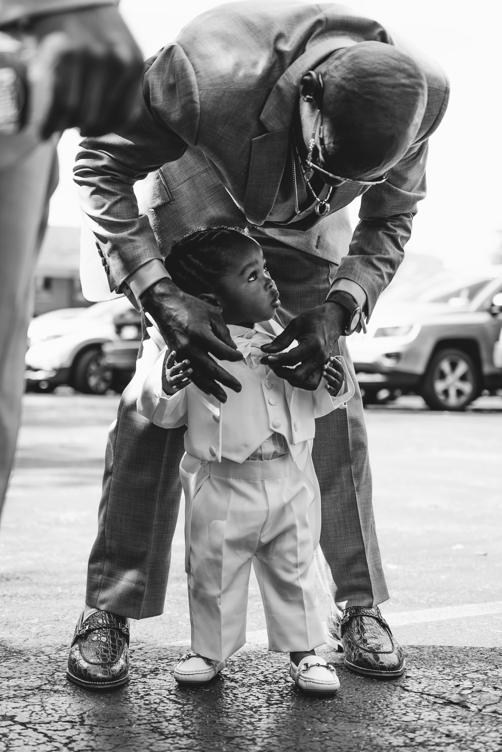 grayscale photo of man fixing boy suit