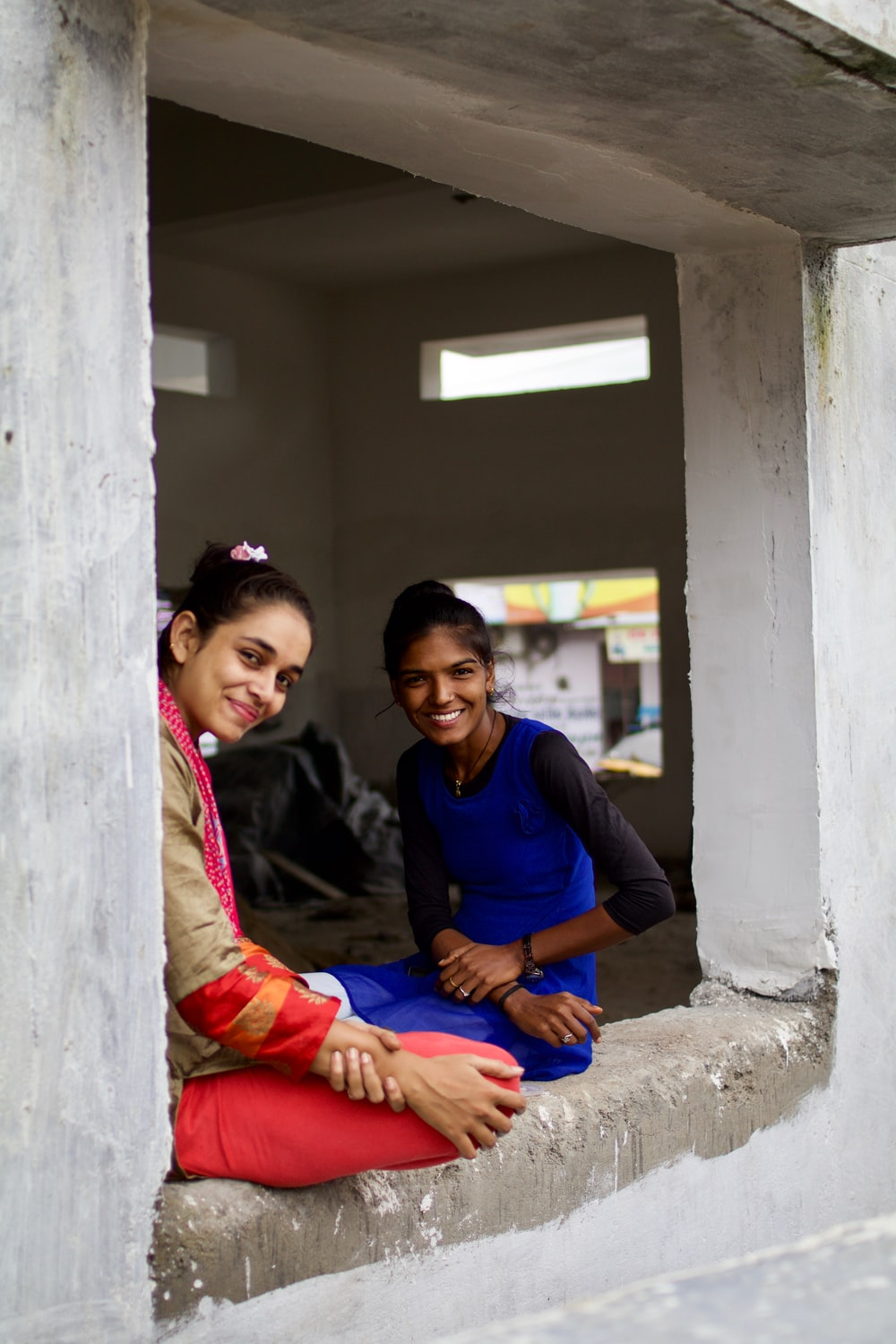 two smiling women sitting on window sill