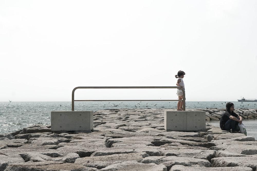 woman and girl near ocean