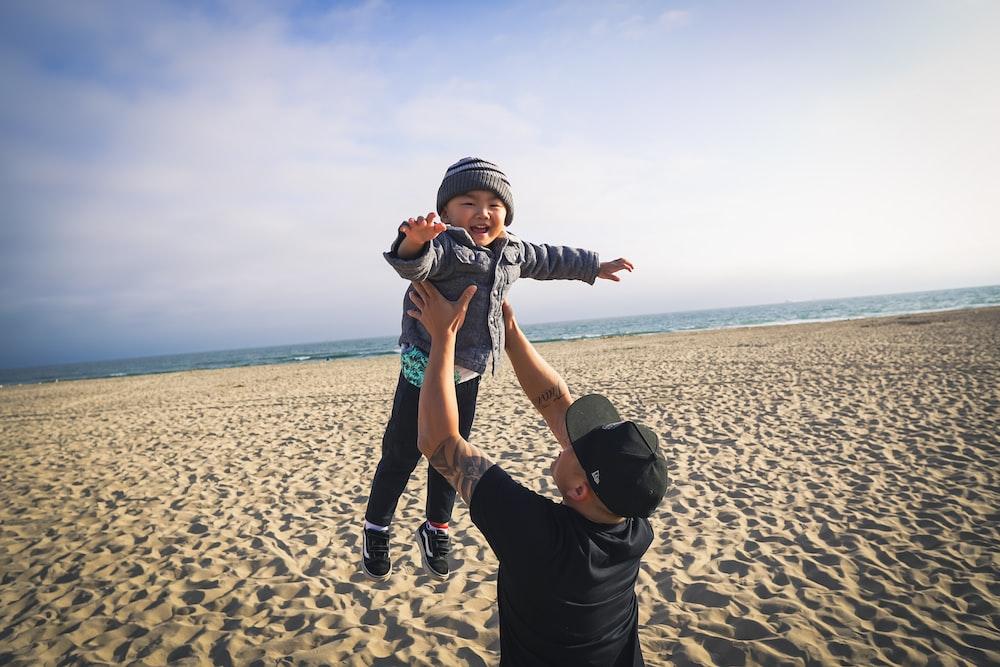 man carries the boy near seashore