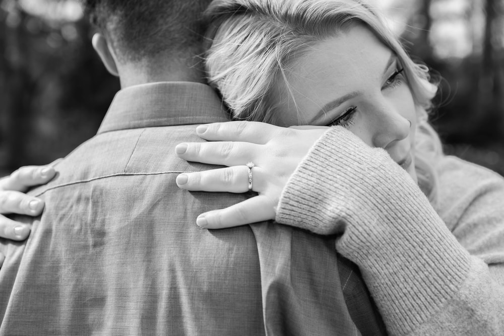 grayscale photography of man and woman hugging