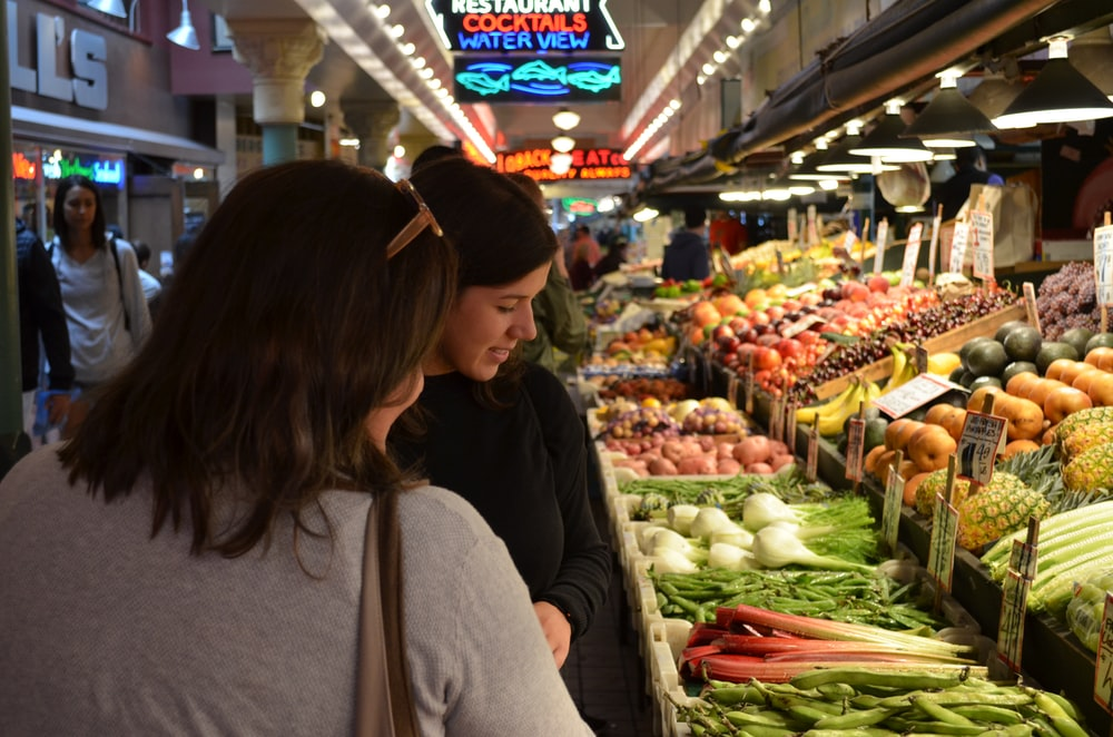 two woman standing beside vegetable display