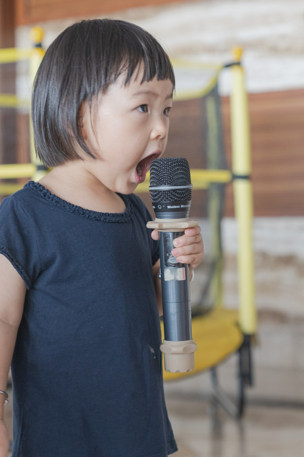 girl in black blouse olding microphone