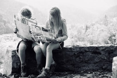 grayscale photo of boy and girl reading newspaper