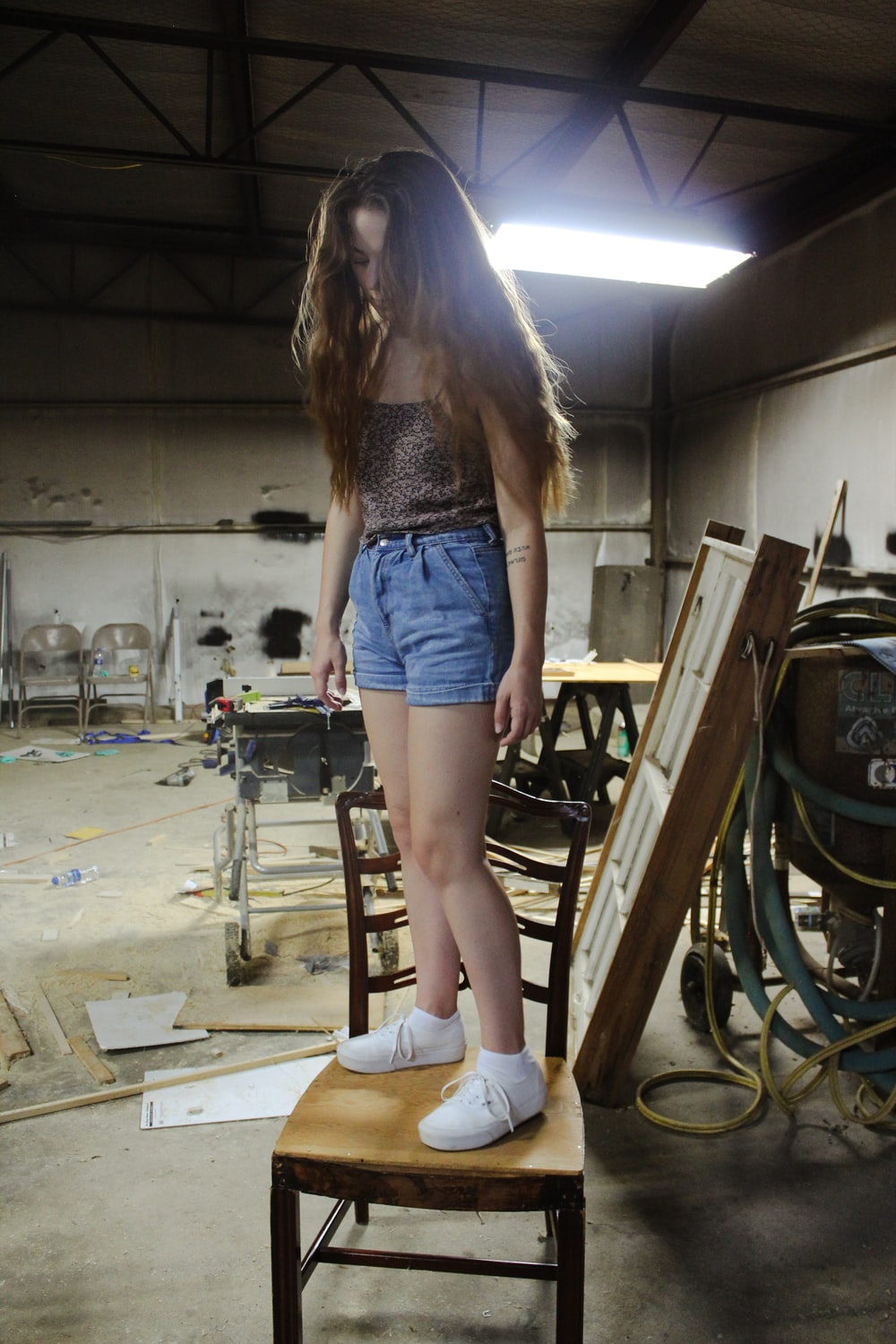 girl wearing blue shorts on brown wooden chair