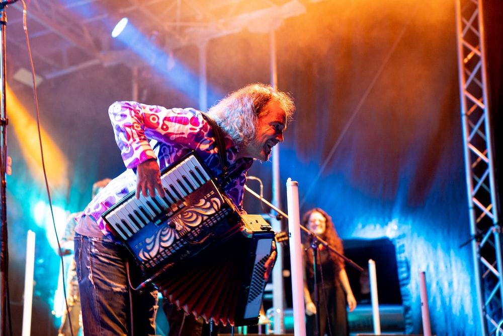 man playing accordion near woman