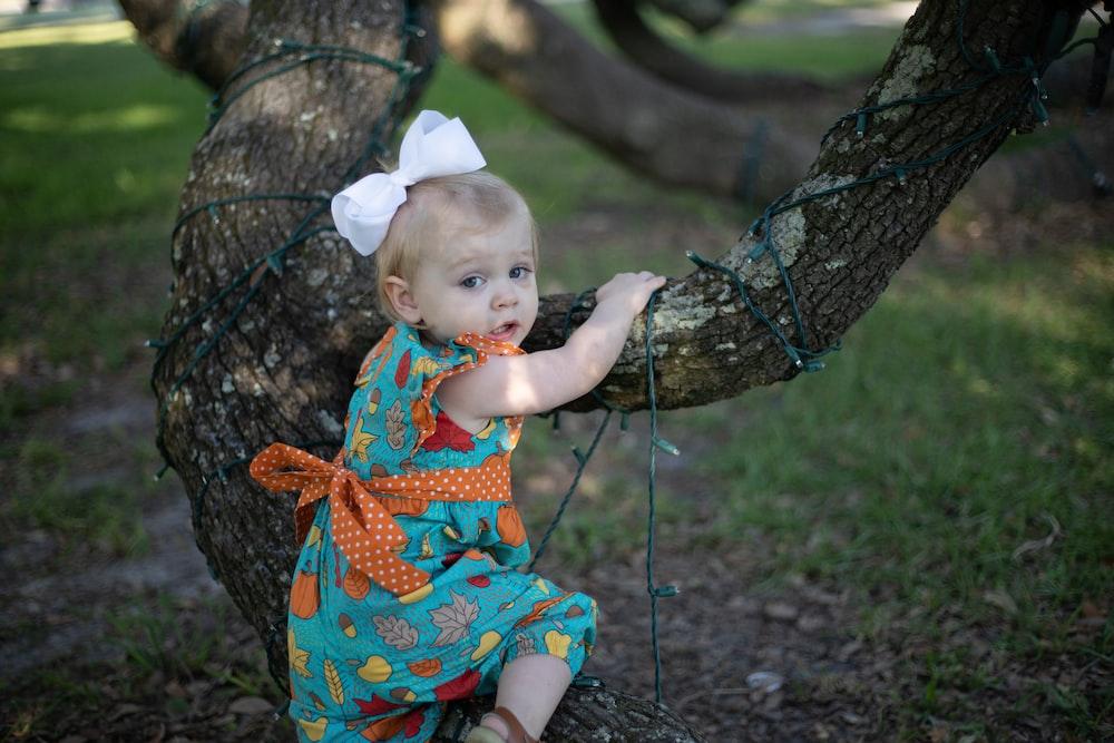 girl in blue, yellow, and orange fruit print sleeveless dress climbing tree