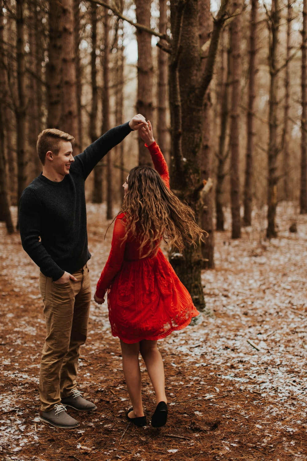 smiling woman and man dancing near trees
