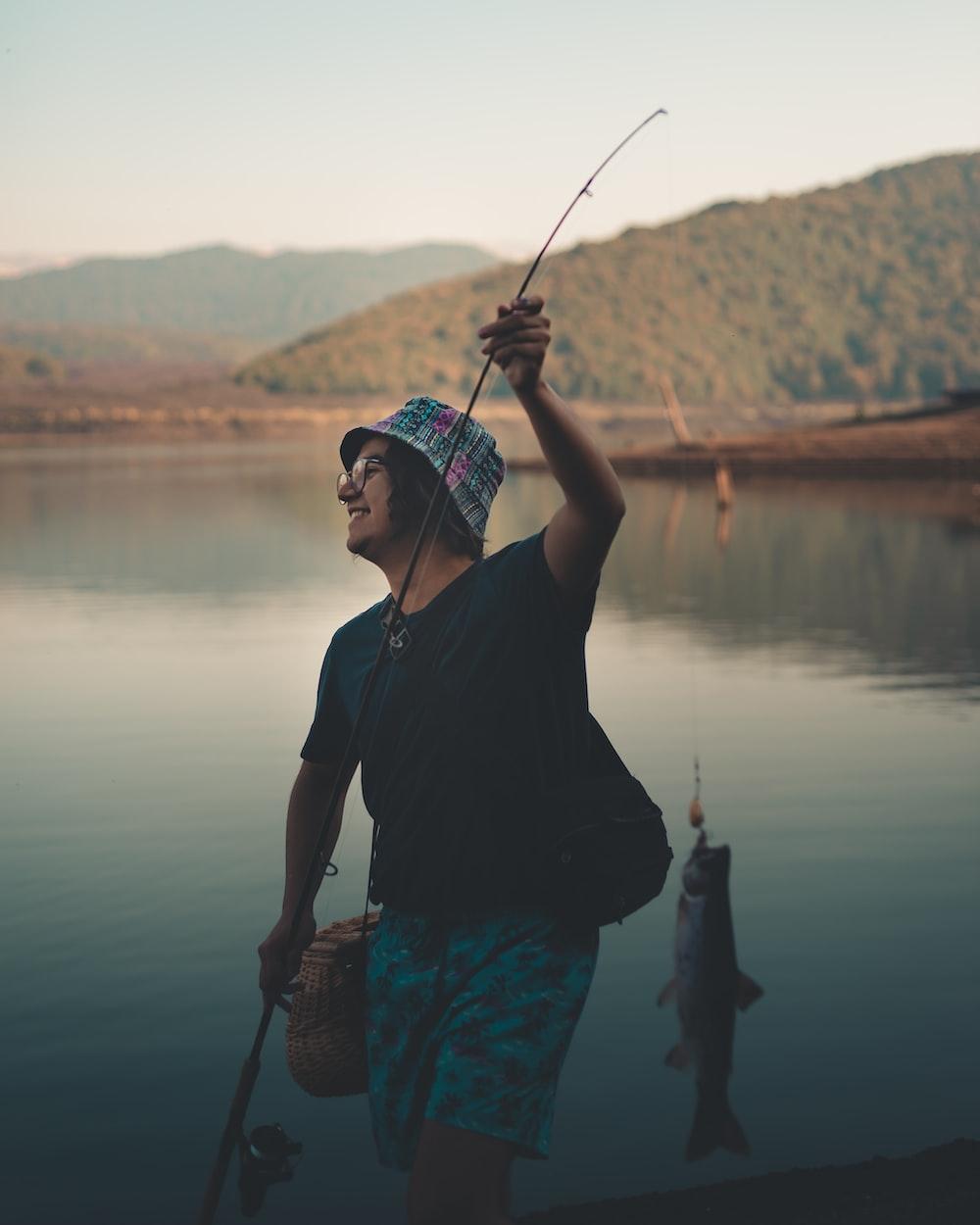 man wearing black shirt holding fishing rod while standing near lake