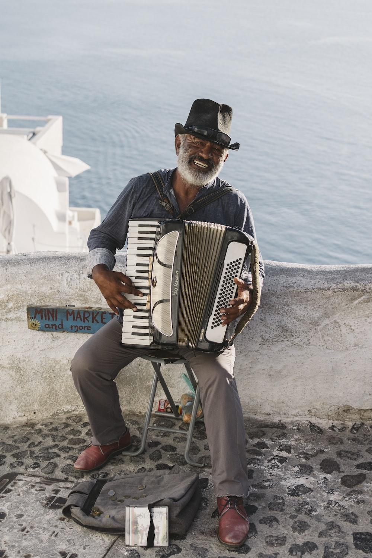 man playing white accordion