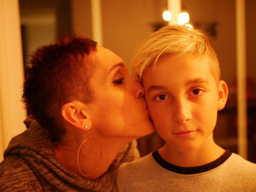 woman kissing boy's cheek