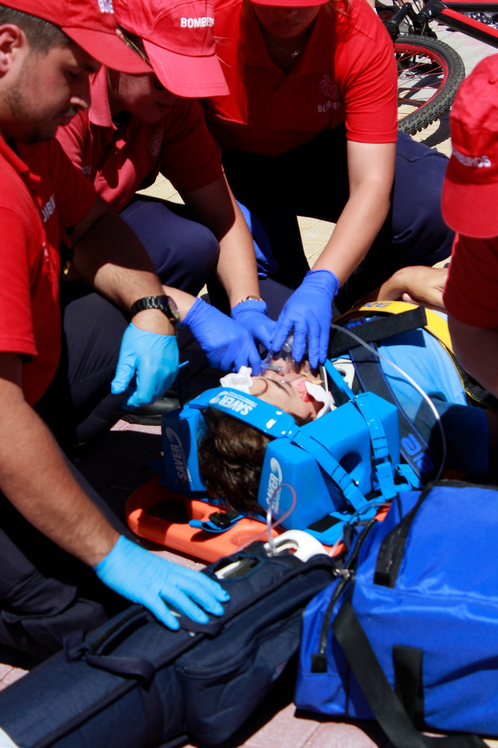 people performing first aid medical care to an injured man