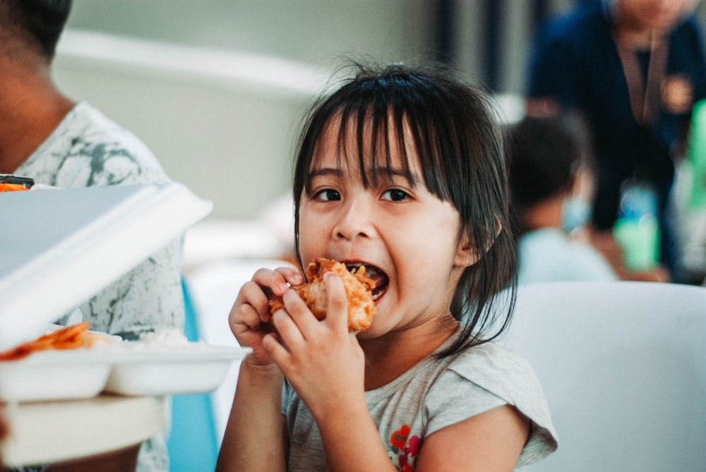 girl biting a good by table at daytime